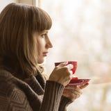 年轻俏丽的在窗口附近的妇女饮用的咖啡在咖啡馆 库存图片