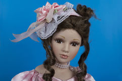 俏丽的在蓝色背景的玩偶面孔佩带的帽子 库存图片