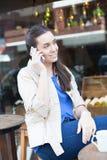 俏丽的在街道的妇女饮用的咖啡 库存照片