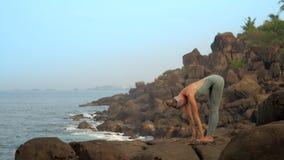 俏丽的夫人在uttanasana姿势站立在海洋慢动作 股票视频