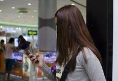 俏丽的夫人头发用在百货商店里面的智能手机报道面孔正文消息 免版税库存照片