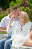 俏丽的夫妇和容忍坐一条长凳在公园户外 免版税库存照片