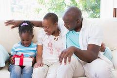 俏丽的夫妇提供他们的女儿的一presente 免版税库存照片