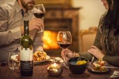 俏丽的夫妇饮用的红酒和吃在餐馆,冬时,浪漫晚餐 库存照片