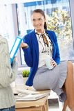俏丽的女勤杂工坐服务台聊天 免版税库存图片