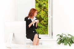 俏丽的女勤杂工坐窗台 免版税库存图片
