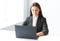 俏丽的女商人画象有膝上型计算机的在offic 库存图片