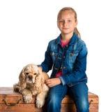 俏丽的女孩与美国西班牙猎狗坐木胸口 免版税图库摄影