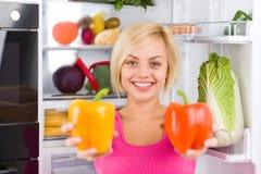 俏丽的女孩举行红色黄色胡椒,冰箱 免版税库存图片