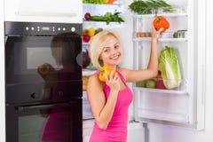 俏丽的女孩举行红色黄色胡椒,冰箱 库存照片