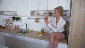 俏丽的女孩使用在互联网上的智能手机并且吃土豆片坐厨房用桌表面  股票录像