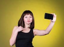 俏丽的女孩做一张鸭子面孔,并且采取与她巧妙的电话的一张自画象 性感的深色的制造的selfie 库存图片