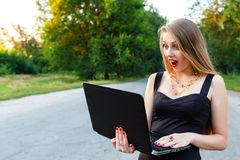 俏丽的女孩凝视膝上型计算机,当在路时 免版税库存照片