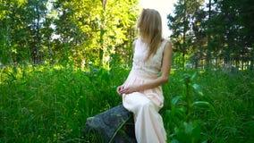 俏丽的女孩单独坐一个岩石在公园 股票录像