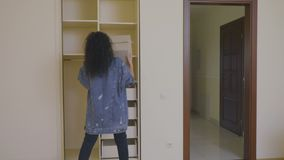 俏丽的女孩在一个空的衣橱投入了有事的一个箱子在一个新房里 股票录像