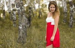 俏丽的女孩在一个美丽的森林里 库存照片