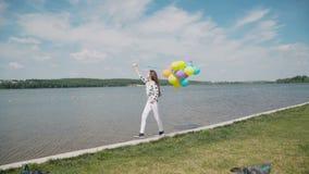 俏丽的女孩在与五颜六色的气球的河海湾在水走并且看 影视素材