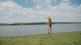 俏丽的女孩在与五颜六色的气球的河海湾在水走并且看 股票视频