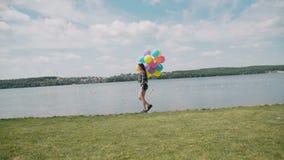 俏丽的女孩在与五颜六色的气球的河海湾在水走并且看 股票录像
