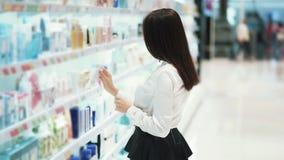 俏丽的女孩在化妆用品商店选择奶油色,看物品,慢动作 股票视频