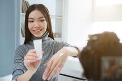 俏丽的女孩在接近窗口的一间屋子里坐并且看对照相机 她微笑着 年轻博客作者显示 免版税图库摄影