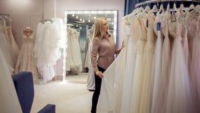 俏丽的女孩在新娘商店选择婚礼服 少妇企业家 免版税库存照片
