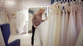 俏丽的女孩在新娘商店选择婚礼服 少妇企业家 免版税库存图片