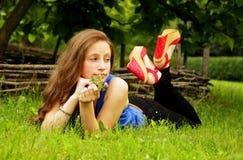 俏丽的女孩在有绿草的草坪说谎并且调查距离 免版税库存照片