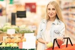 俏丽的女孩在水果市场上用各种各样的五颜六色的新鲜的水果和蔬菜 在倾吐的餐馆沙拉的主厨概念食物新鲜的厨房油橄榄 免版税库存图片