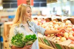 俏丽的女孩在水果市场上用各种各样的五颜六色的新鲜的水果和蔬菜 在倾吐的餐馆沙拉的主厨概念食物新鲜的厨房油橄榄 免版税图库摄影