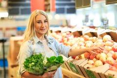 俏丽的女孩在水果市场上用各种各样的五颜六色的新鲜的水果和蔬菜 在倾吐的餐馆沙拉的主厨概念食物新鲜的厨房油橄榄 免版税库存照片