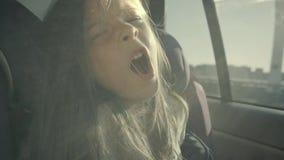 俏丽的女孩在汽车坐并且开始打呵欠 她看起来轻松和愉快在slo mo 股票视频