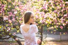 年轻俏丽的女孩在美丽的庭院里放松 意想不到的桃红色木兰 免版税库存图片