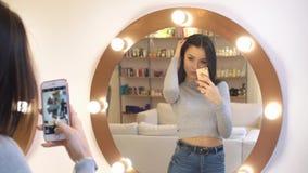 年轻俏丽的女孩在镜子前拍照片她自己 她与意想不到的反射的美容院的在她 股票录像