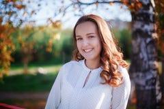 年轻俏丽的女孩在阳光下,秋天公园画象  库存图片