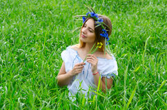 俏丽的女孩在绿色麦子耳朵中的领域坐 库存图片