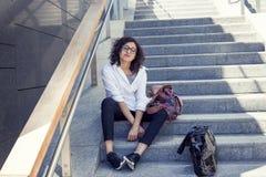 俏丽的女孩坐一架梯子在中心 免版税库存图片