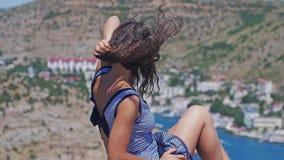 俏丽的女孩坐在高度并且敬佩在山的背景的美好的自然 风打击 股票录像