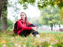 俏丽的女孩坐秋叶 免版税库存照片