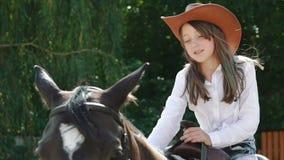 俏丽的女孩坐马,微笑和爱抚它 迟缓地 股票视频