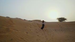 俏丽的女孩奔跑在沙漠 美丽的妇女跑在日落 慢的行动 影视素材