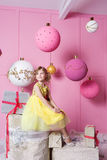 俏丽的女孩孩子在一件黄色礼服的6岁 婴孩在蔷薇石英室装饰了假日 免版税库存图片
