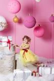 俏丽的女孩孩子在一件黄色礼服的6岁 婴孩在蔷薇石英室装饰了假日 免版税库存照片
