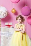 俏丽的女孩孩子在一件黄色礼服的6岁 婴孩在蔷薇石英室装饰了假日 免版税图库摄影