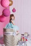 俏丽的女孩孩子在一件蓝色礼服的4岁 婴孩在蔷薇石英室装饰了假日 免版税库存照片