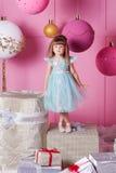 俏丽的女孩孩子在一件蓝色礼服的4岁 婴孩在蔷薇石英室装饰了假日 免版税库存图片