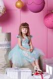 俏丽的女孩孩子在一件蓝色礼服的4岁 婴孩在蔷薇石英室装饰了假日 免版税图库摄影
