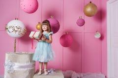 俏丽的女孩孩子在一件蓝色礼服的4岁 婴孩在他们的手上的拿着礼物 蔷薇石英室装饰了假日 库存照片