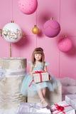 俏丽的女孩孩子在一件蓝色礼服的4岁 婴孩在他们的手上的拿着礼物 蔷薇石英室装饰了假日 免版税库存照片