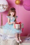 俏丽的女孩孩子在一件蓝色礼服的4岁 婴孩在他们的手上的拿着礼物 蔷薇石英室装饰了假日 免版税库存图片